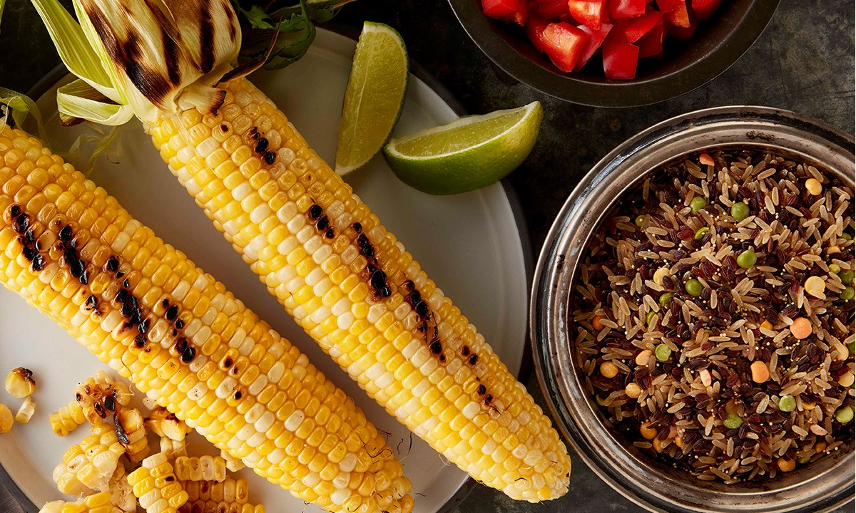 Overhead of grilled corn and grains in bowl