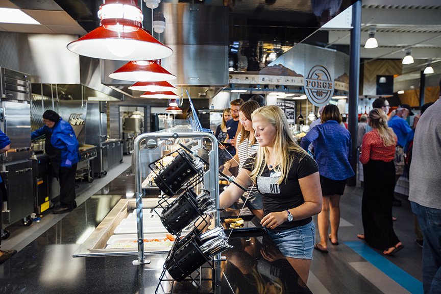 Student putting food on their plate at Montana State University's new dining pavilion